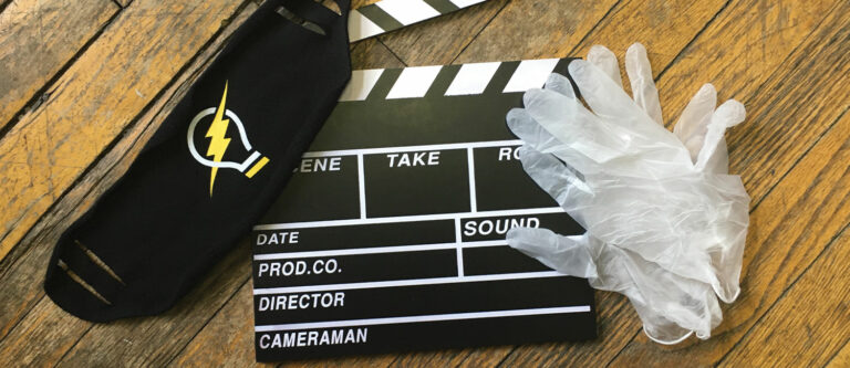 Mask and sanitary gloves laying on top of a slate that's used to mark different video takes. This was used in a blog Current360 created about video production during a pandemic.