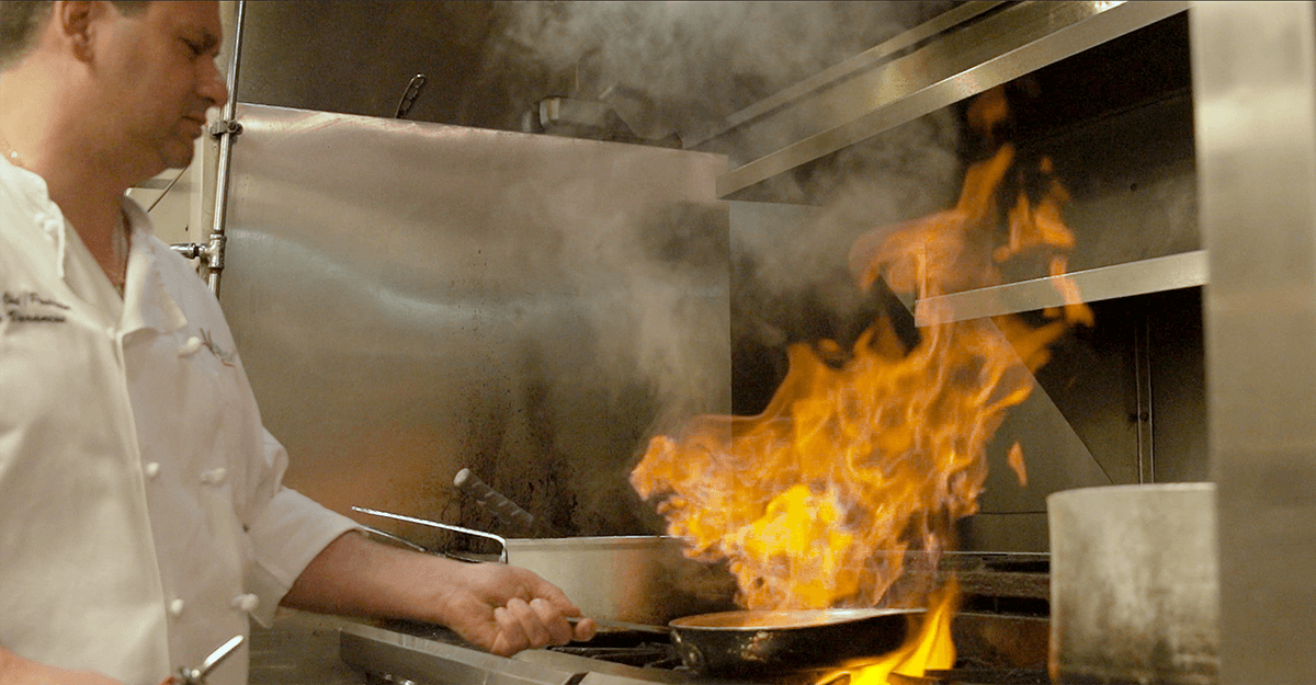 A chef wearing a white chef's shirt shaking a pan with flames coming out. Current360 created videos featuring prominent Louisville business owners who use Commonwealth Bank & Trust for commercial banking.