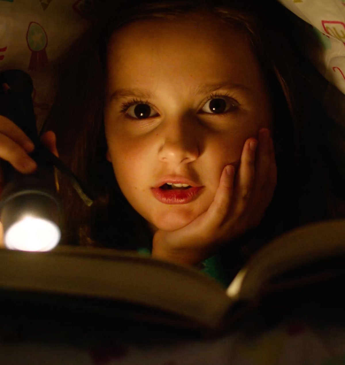 Young girl in bed with a flashlight reading in a Papa John's commercial. This TV commercial was produced by Current360 as part of an integrated marketing campaign featuring broadcast TV, social marketing, media planning.